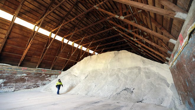 Brown County Public Work Highway Division Operations Manager Mike Piacenti walks at the foot of a salt pile inside one of three salt barns at the county facility on Glendale Avenue in Howard.