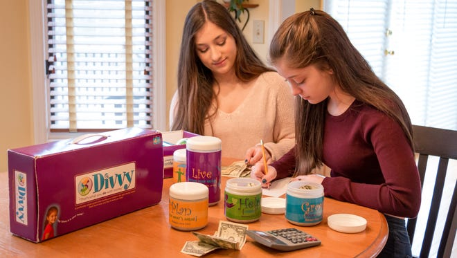 Maddie and Brooke Baccarella,16-year-old twins in Asheville, have been managing their personal money portfolios since third grade using the simple Divvy method. The Divvy kit they're using — developed by their mom and a business partner — is no longer on the market, but you can replicate a DIY version with a shoe box and jars.