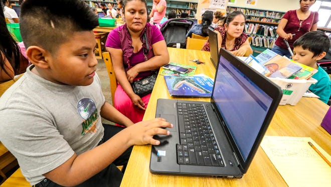 Nelson Mejia-Us takes a comprehension test on the computer as his mother, Catarina Us Imul,  looks on. Reading Blast event, Saturday, Jan. 21, at Orange River Elementary, is an example of what one of Lee's schools is doing to bring parents on campus in a laid-back, reading-focused event.  About 100 students and parents go into the library, select books to check out and provide opportunity for the kids to read to their parents in English.