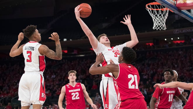 Rutgers center C.J. Gettys (34) goes to the basket past Wisconsin guard Khalil Iverson (21)