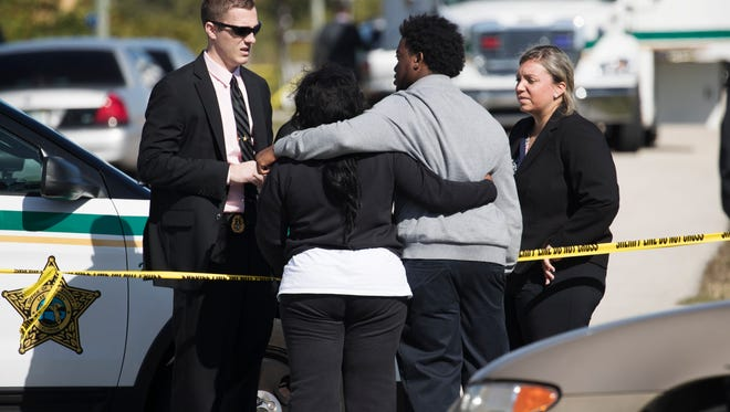 Members of the Lee County Sheriff's Office talk to members of Jontavious Thomas' family on Monday. Thomas was killed at his Lehigh Acres residence. His death is being investigated as a homicide.