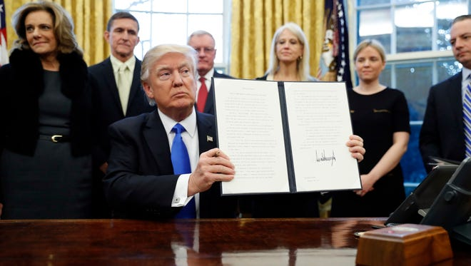 President Donald Trump holds up a signed Executive Order in the Oval Office of the White House, Saturday, Jan. 28, 2017 in Washington. (AP Photo/Alex Brandon)