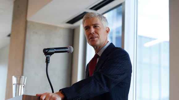 In this Friday, Jan. 27, 2017, photograph, 10th U.S. Circuit Court of Appeals Judge Neil Gorsuch makes a point while delivering prepared remarks before a group of attorneys at a luncheon in a legal firm in lower downtown Denver.
