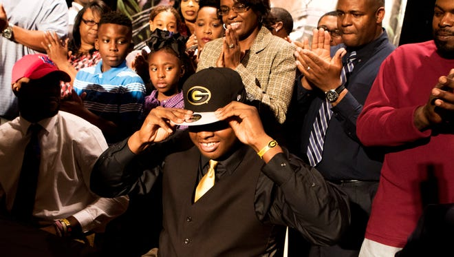 Neville offensive lineman Kyle Davis puts a Grambling hat on as he poses for television cameras after signing his commitment to play for the Tigers next year on National Signing Day on Wednesday, February 1, 2017.