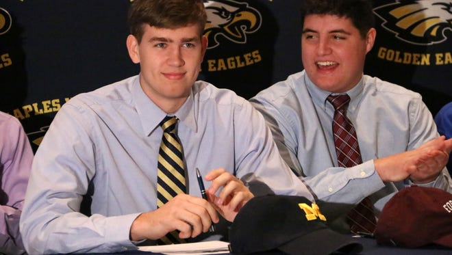 Chris Hanlon smiles after signing his national letter of intent to play with the University of Michigan football program after being offered a preferred walk-on spot on Friday. Six Naples athletes signed their NLI's Wednesday morning as part of National Signing Day.