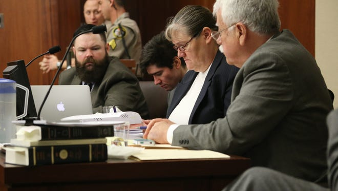 Defense team members, from right, Gary Pendleton, Mary Corporon, Brandon Smith and J.D. Lauritzen review heavily redacted deposition testimony during Smith's trial on aggravated murder and aggravated assault charges Wednesday.