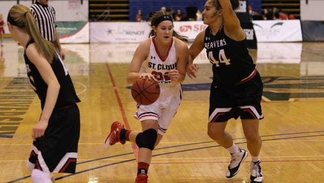 St. Cloud State's Amanda Christianson (32) dribbles the ball as Minot State's Diondra Denton (44) defends Saturday afternoon.