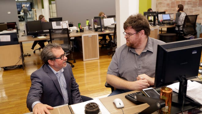 Lou Hoffman, at left, CEO of The Hoffman Agency, a public relations firm, talks with employee Matthew Burrows in his company's office, in San Jose, Calif. After President Donald Trump issued an executive order restraining immigration from seven Muslim countries, staffers at the marketing company started worrying about a co-worker from one of those nations who's in the process of applying for a green card. The employees were concerned that she might be sent back to that country.