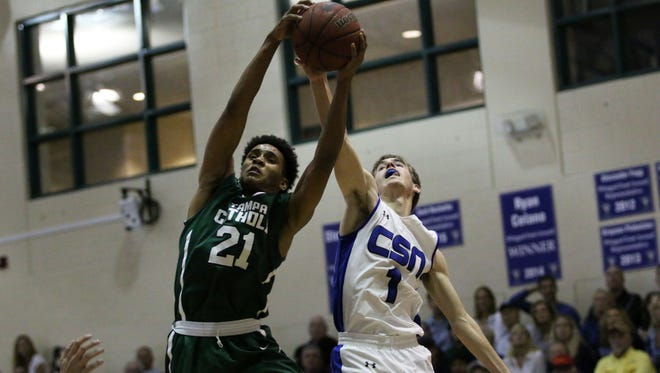 Tai Strickland, left, and Connor Foxhoven reach for the rebound during the 5A regional semifinal between CSN and Tampa Catholic at Community School of Naples on Tuesday, Feb. 21, 2017. Tampa Catholic defeated the Seahawks 64-60.