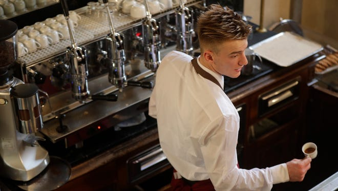 "A waiter dishing an espresso for a customer at a traditional coffee bar in Milan, Italy, on Monday. Longtime CEO Howard Schultz's vision for Starbucks was largely inspired by the Milan coffee bars he experienced on his first trip to the northern Italian city in 1983. Schultz will continue on with the company to open ""'the quintessential Roastery"" in Milan by the end of 2018."