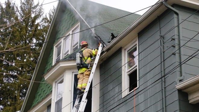 A firefighter helps extinguish a fire at a student rental home at 711 East State St.