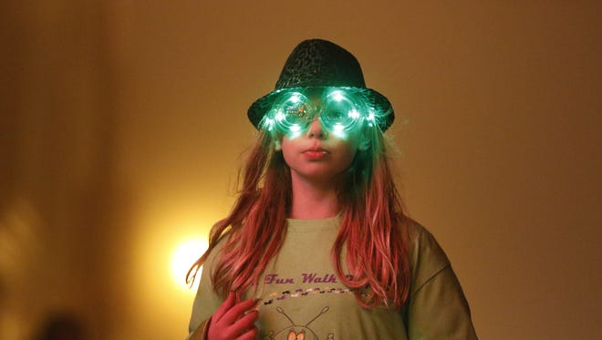 A parade participant wears glowing green goggles walking down South Eighth Street as a part of the 18th annual St. Patrick's Day Parade in downtown Manitowoc in 2016.