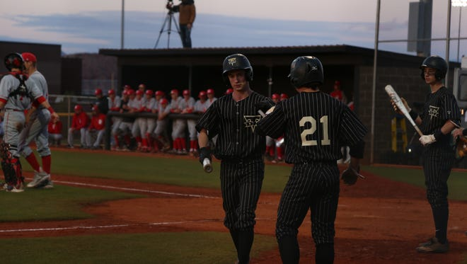 Desert Hills' Trey Allred (left) fist bumps teammate Sam Rhoton after Allred scores a run during the Thunder's loss to Spanish Fork, March 23, 2017.