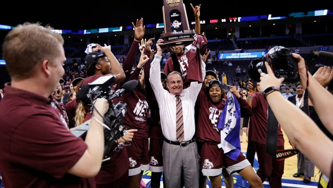 Mississippi State head coach Vic Schaefer holds up the championship trophy as he celebrates with his team after a regional final of the NCAA women's college basketball tournament against Baylor, Sunday, March 26, 2017, in Oklahoma City. Mississippi State won 94-85. (AP Photo/Alonzo Adams)