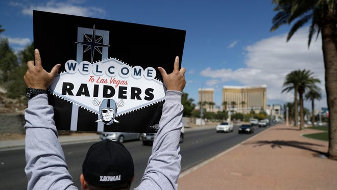 A man celebrates holding a Raiders sign, Monday, March 27, 2017, in Las Vegas. NFL team owners approved the move of the Raiders to Las Vegas in a vote at an NFL football annual meeting in Phoenix.