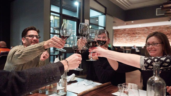 Friends give a celebratory toast during a dinner at RARE Italian in Fort Collins.