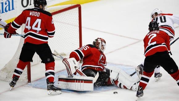 New Jersey Devils goalie Cory Schneider, center, stops