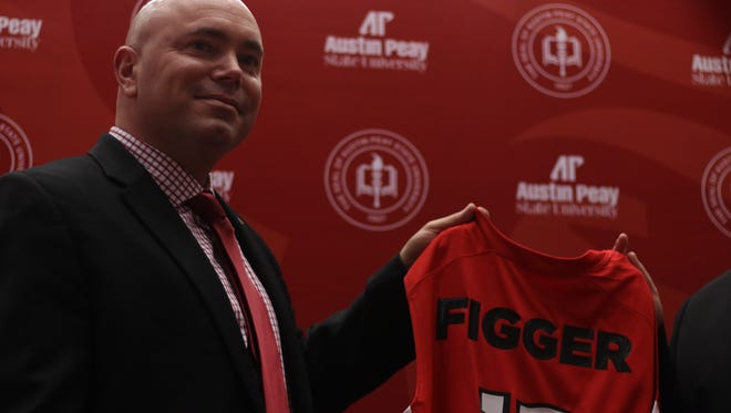 Matt Figger poses for photos with a jersey following his introductory press conference Thursday.