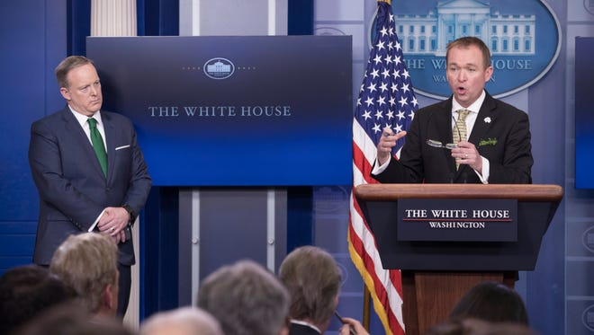 Director of the White House Office of Management and Budget Mick Mulvaney participates in a news conference as White House Press Secretary Sean Spicer looks on March 16, 2017.