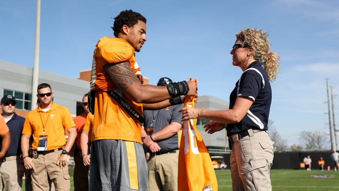 Tennessee linebacker Cortez McDowell  presents Capt. Sharon Moore of the Maryville Police Department with a jersey honoring fallen officer Kenny Moats on April 13, 2017,  at Haslam Field.