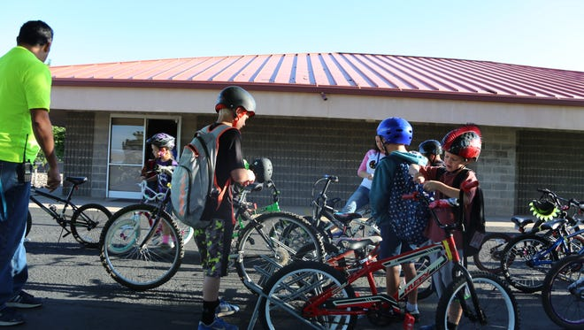 Students at Sunset Elementary School arrive on bicycles for their classes in this April file photo.