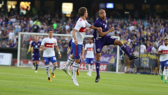 Louisville City FC's Luke Spencer goes up for a header with a Toronto FC defender.