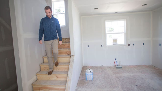 Zach Christopoulos, 24, of Northville, Michigan, descends from the master bedroom of his new-construction townhouse in Wixom, Michigan on May 7, 2017.