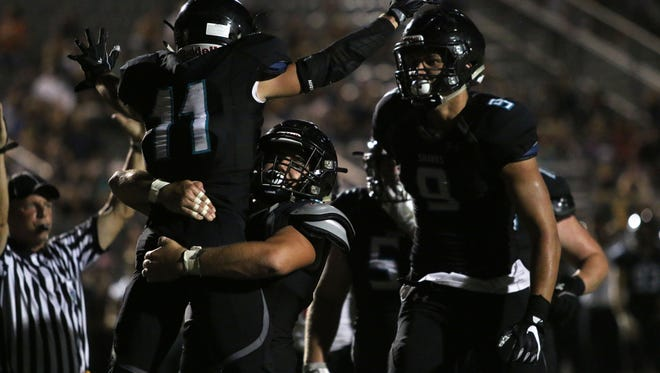 Derek Sobel (11) celebrates with Niko Perovic and teammates after scoring his second touchdown of the night during Friday night's spring game between Gulf Coast and Sarasota in Naples. Gulf Coast blew past the Sailors with a 35-0 win.