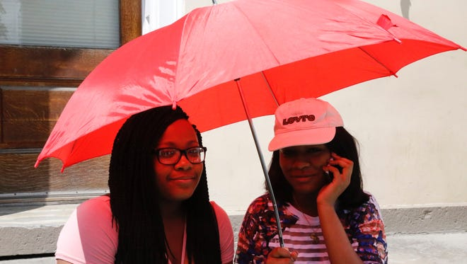 (Left to right) Ithaca residents Saharah Rowser and La'Brae Isaac sit under an umbrella outside the Clinton House.