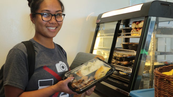 Senior Kreeshia Aquino purchases a bento box at the new Triton Express located in Dorm 1 on the University of Guam campus.