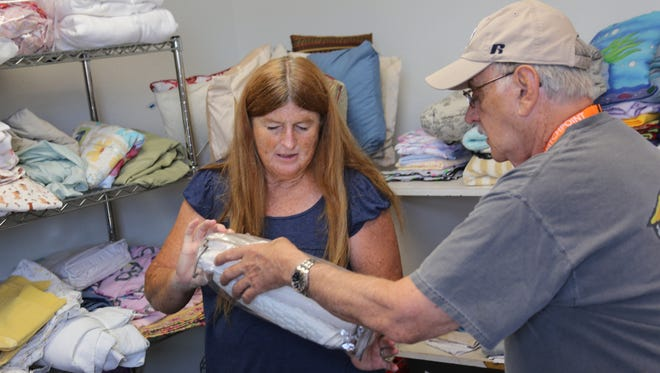 Thayes and George Hewitt sort through linens as they volunteer at the Switchpoint thrift store in St. George.