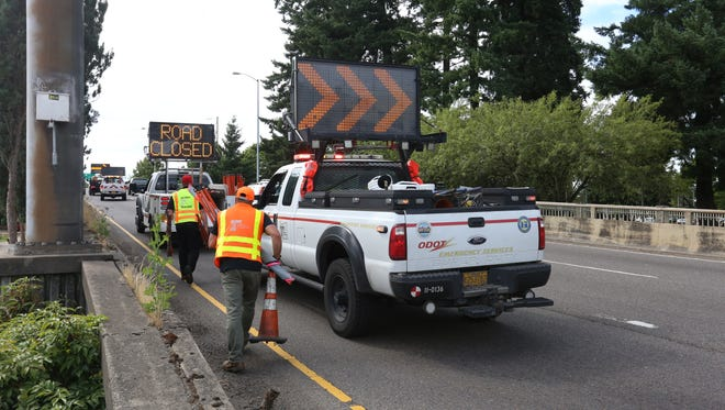 Oregon Department of Transportation officials clear equipment from the Marion Street bridge in Salem after a crash on Highway 22 brought traffic to a standstill on Saturday, June 17, 2017.