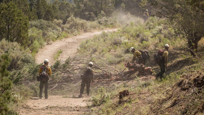 Firefighters work to brush-up an indirect line of the Brian Head fire.