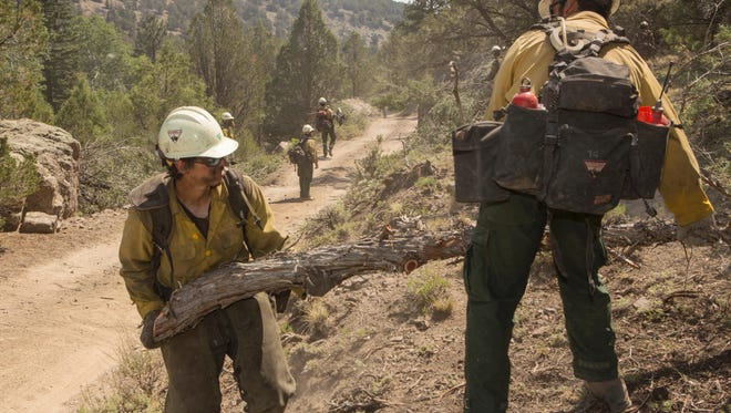 Firefighters clearing debris from the line of the Brian Head fire.