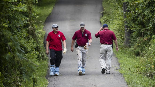 Investigators walk along a blocked off drive way in Solebury, Pa., during the search for four missing young Pennsylvania men feared to be the victims of foul play.