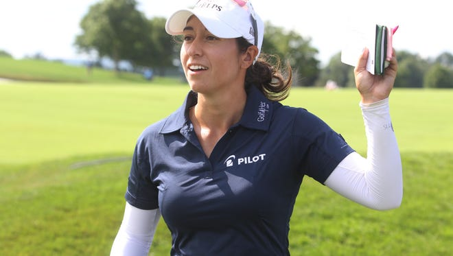 Marina Alex waves to supporters as she heads to the 10th tee.