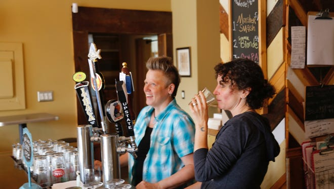 Amelia Sauter, right, drinks one of the craft beers at Felicia's Atomic Brewhouse and Bakery. She is joined by fellow co-owner Leah Houghtaling.