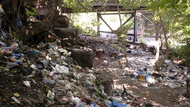 Trash including syringes lay among other discarded items near train tracks in Philadelphia, Workers are preparing to clean up the open-air heroin market that has thrived for decades along a set of train tracks a few miles outside the heart of Philadelphia.