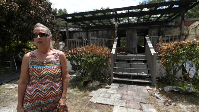 Theresa Parsons stands outside of her family's home on Elena Drive where an early Tuesday morning fire consumed the house and burned nearly all of their belongings.