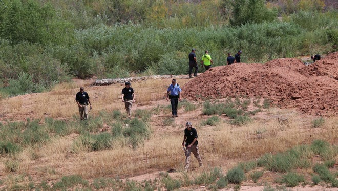 St. George Police investigators walk through a field north of the Tonaquint Cemetery after a dead woman's body was found in a wash near the Santa Clara River there early Saturday, Aug. 5, 2017.