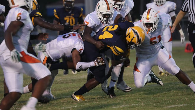 Dunbar players (from left) Justin Michel, Peter Jean and Judas McKenzie swarm Lehigh running back Chris Curry during a game on Aug. 31.