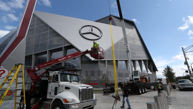 Crews work to complete the signage on Mercedes-Benz Stadiumin Atlanta where the Chick-fil-A kick-off game between FSU and Alabama will take place Saturday, Sept. 2, 2017.