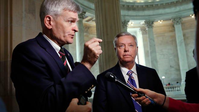 Sen. Bill Cassidy, R-La., left, and Sen. Lindsey Graham, R-S.C. talk about healthcare, Thursday, July 13, 2017, on Capitol Hill in Washington.