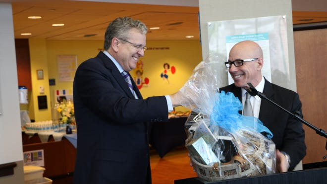 Joseph W. Devine, president and CEO of Kennedy Health, gives a basket of New Jersey-themed items to Dr. Stephen Klasko, president and CEO of Jefferson Health. The two signed a ceremonial agreement Thursday to mark the official merger of the two health systems.
