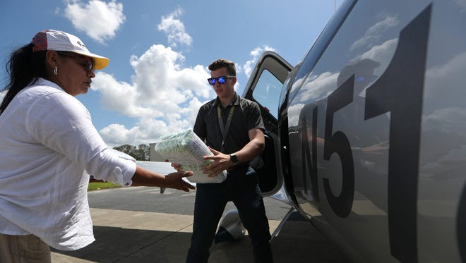 Pilot Dylan Leoni hands off diapers from a freight load of supplies, including water, childcare products and food to Dora Chavez a resident of LaBelle, Fla. where stores and gas stations have been slow to recover from Hurricane Irma. LaBelle, a rural town just inland from Fort Myers, is home to a population of less than 5,000, many of which are migrant farm workers with few resources.