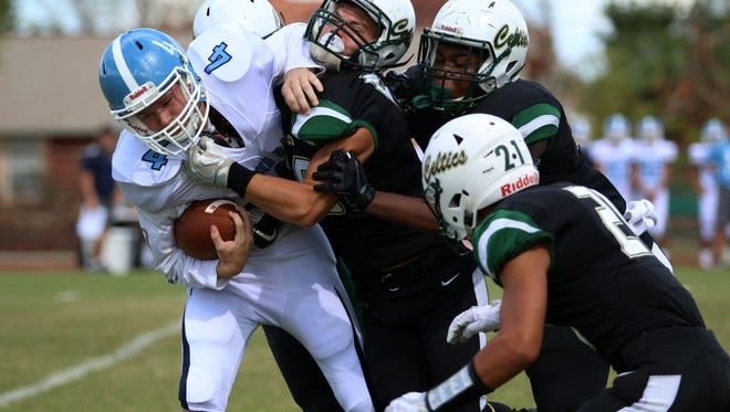 Kyler Howard (4) is sacked by the St. John Neumann defense during Saturday afternoon's game between Marco Island Academy and St. John Neumann.