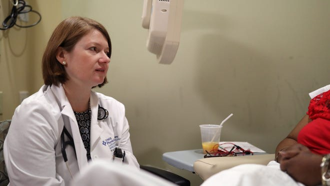 Dr. Karen Russell, a cancer and hematology specialist at Tallahassee Memorial HealthCare, speaks with a breast cancer patient at the chemotherapy infusion and exam area of the Cancer Center of the hospital.