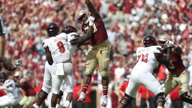 FSU's Demarcus Christmas leaps up trying to block a pass by Louisville's Lamar Jackson during their game at Doak Campbell Stadium on Saturday, Oct. 21, 2017.