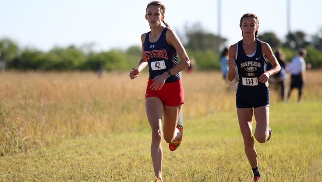 Estero's Alayna Goll (left) and Naples' Jillian Dempsey stay neck and neck with each other during the Class 3A-12 district meet at Palmetto Ridge High School on Thursday, Oct. 26, 2017.
