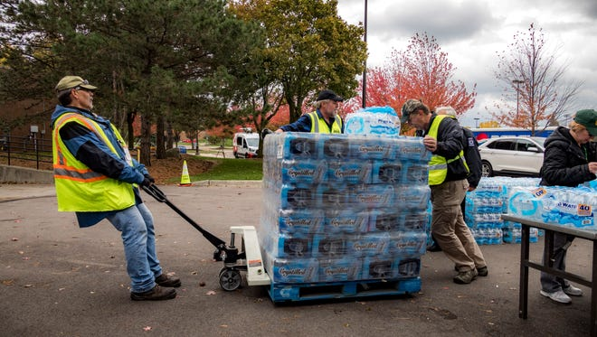Novi Community Emergency Response Team member Rich Artuna pulls a pallet of bottled water to be distributed during the advisory.